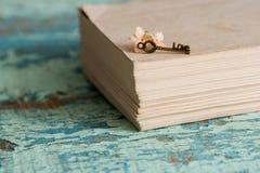 美丽的静物画闭合的书籍,华伦泰` s天的关键标志 葡萄酒老心脏 在织地不很细蓝绿色背景与 免版税库存照片
