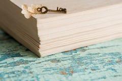 美丽的静物画闭合的书籍,华伦泰` s天的关键标志 葡萄酒老心脏 在织地不很细蓝绿色背景与 库存图片