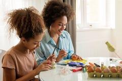 美丽的非裔美国人的上色复活节彩蛋的妇女和她的女儿 免版税库存照片