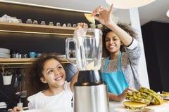 美丽的非裔美国人的妇女和她的女儿切口在厨房里结果实 库存照片