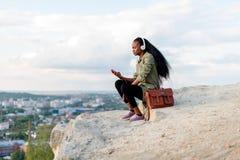 美丽的非裔美国人的有智能手机和耳机的行家少妇听到在蓝色多云天空的音乐的 免版税库存照片