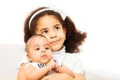 美丽的非洲女孩抱着胳膊的姐妹婴孩 免版税图库摄影