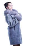 蓝蓝冬天貂皮大衣的美丽的妇女 免版税库存照片