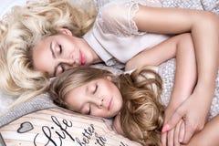 美丽的面孔的和惊人的眼睛谎言睡觉在一张床上的美丽的白肤金发的妇女母亲和女儿的画象在eleg 图库摄影