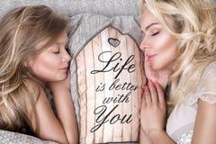 美丽的面孔的和惊人的眼睛谎言睡觉在一张床上的美丽的白肤金发的妇女母亲和女儿的画象在eleg 免版税图库摄影