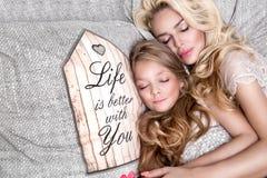 美丽的面孔的和惊人的眼睛谎言睡觉在一张床上的美丽的白肤金发的妇女母亲和女儿的画象在eleg 库存图片