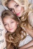 美丽的面孔的和惊人的眼睛谎言睡觉在一张床上的美丽的白肤金发的妇女母亲和女儿的画象在eleg 免版税库存照片