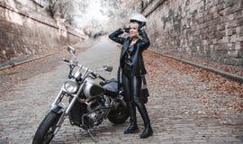 美丽的骑自行车的人妇女室外与摩托车 免版税图库摄影