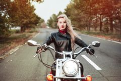 美丽的骑自行车的人妇女室外与摩托车 库存图片