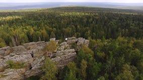 美丽的高石岩石在天空蔚蓝下的绿色森林里 英尺长度 人身分顶视图在岩石的以厚实的绿色 股票视频