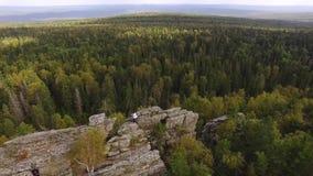 美丽的高石岩石在天空蔚蓝下的绿色森林里 英尺长度 人身分顶视图在岩石的以厚实的绿色 影视素材
