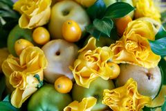 美丽的黄色玫瑰、苹果和金桔以果子花束的形式作为礼物 免版税库存照片