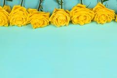 美丽的黄色玫瑰的装饰在蓝色背景的 免版税图库摄影