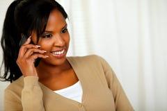 美丽的黑人妇女交谈在移动电话 免版税库存图片