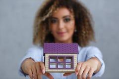 美丽的黑人妇女画象 拿着一个微型玩具小家家 免版税库存图片