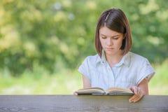 美丽的读书浅黑肤色的男人女孩画象  免版税库存图片