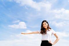 美丽的年轻亚裔大学或大学生提出姿势,在蓝天bac的拷贝空间的妇女做广告的或产品 库存照片
