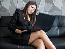 美丽的年轻亚洲女商人坐沙发,与观看桌面显示器的便携式计算机和穿戴黑衣服一起使用 免版税库存照片