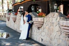 美丽的年轻亲吻在石墙附近的新娘和新郎在公园 在爱的婚礼夫妇wedd天 图库摄影
