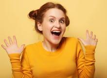 美丽的年轻人使在黄色背景的redhair妇女惊奇 库存照片