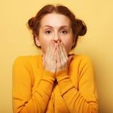 美丽的年轻人使在黄色背景的redhair妇女惊奇 免版税库存图片