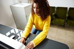 年轻美丽的黑人女孩在家庭办公室工作 图库摄影