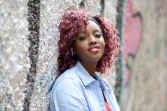 美丽的黑人妇女在与红色头发的都市背景中 免版税库存图片