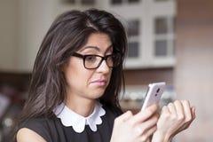 美丽的年轻人接受sms的惊奇的妇女 库存图片