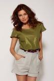 美丽的年轻人有黑暗的卷发的被晒黑的女孩,软的构成在发光的绿色衬衣,与高的腰部的米黄短裤穿戴了 免版税库存图片