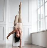 美丽的年轻体操运动员站立单手倾斜在立方体的 巨大时尚和异常的姿势 库存图片