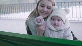 美丽的年轻使用在秋天的长凳的母亲和她可爱的矮小的婴孩停放 影视素材