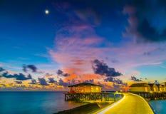 美丽的水别墅在日落的热带马尔代夫海岛 免版税库存照片