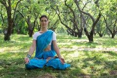 美丽的年轻印地安妇女在莎丽服祈祷和medit穿戴了 免版税库存图片