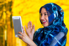 美丽的年轻回教妇女佩带的蓝色上色了hijab,阻止凝视屏幕的片剂,秋天森林背景 免版税库存图片