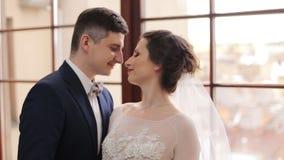 美丽的年轻夫妇新娘和新郎在婚礼礼服看彼此 股票视频