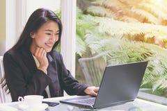 美丽的年轻女商人与膝上型计算机一起使用,看有欣喜姿态的屏幕,震动,惊奇情感 图库摄影