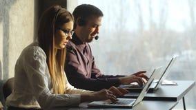 美丽的年轻女商人和英俊的商人侧视图在耳机使用膝上型计算机,当工作在办公室时 股票录像