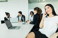 美丽的年轻女实业家微笑和愉快地谈话在期间 免版税库存图片