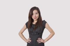 美丽的年轻女实业家画象用在臀部的手在白色背景 库存照片