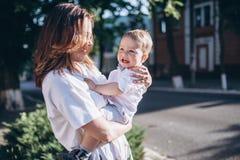 美丽的年轻妈妈和快乐的可爱的白肤金发的男孩使用,获得乐趣 对儿子的妇女神色,他们是微笑的两个 图库摄影
