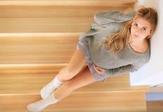 美丽的年轻孕妇坐一架木梯子的步 免版税库存照片