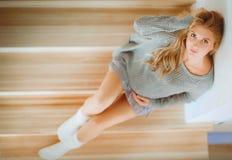 美丽的年轻孕妇坐一架木梯子的步 免版税库存图片