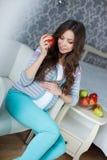 美丽的年轻孕妇用苹果 免版税图库摄影