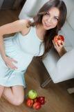 美丽的年轻孕妇用苹果 免版税库存图片
