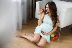 美丽的年轻孕妇用苹果 库存图片