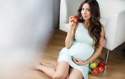 美丽的年轻孕妇用苹果 免版税库存照片