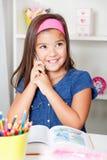 美丽的年轻学校女孩谈话在电话 免版税图库摄影