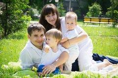 美丽的年轻家庭爸爸妈妈和儿子在说谎 免版税图库摄影