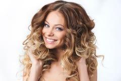 美丽的年轻微笑的女孩画象有丰富头发卷曲的 健康和秀丽 图库摄影