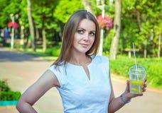 美丽的年轻微笑的妇女,拿着柠檬水鸡尾酒 免版税库存照片